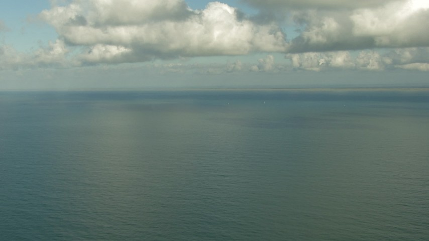 HD stock footage aerial video of the Gulf of Mexico beneath clouds and coastline in the distance, Matagorda Peninsula, Texas Aerial Stock Footage | AF0001_000193