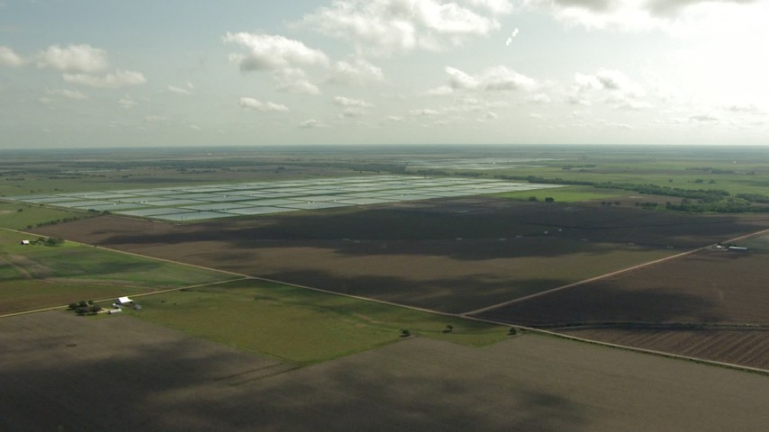 HD stock footage aerial video of flying over farm fields and approach fish farms, Danevang, Texas Aerial Stock Footage | AF0001_000225