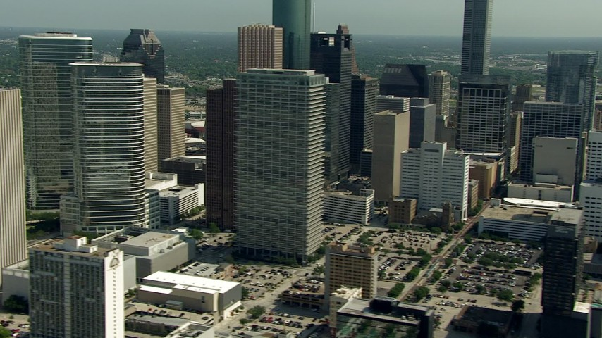 Flyby city skyscrapers to reveal Toyota Center arena and the convention center, Downtown Houston, Texas Aerial Stock Footage AF0001_000266