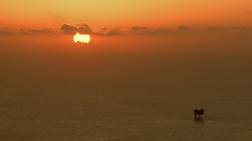 The sun rising behind clouds over an oil platform in the Gulf of Mexico Aerial Stock Footage | AF0001_000339