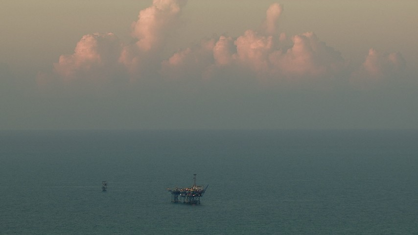 Flyby an oil rig in the Gulf of Mexico at sunrise Aerial Stock Footage AF0001_000345