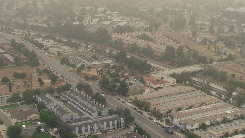 HD stock footage aerial video of a view of Foothill Road, apartment buildings, and the 210 Freeway, on a foggy day, Sylmar, California Aerial Stock Footage | AF0001_000357