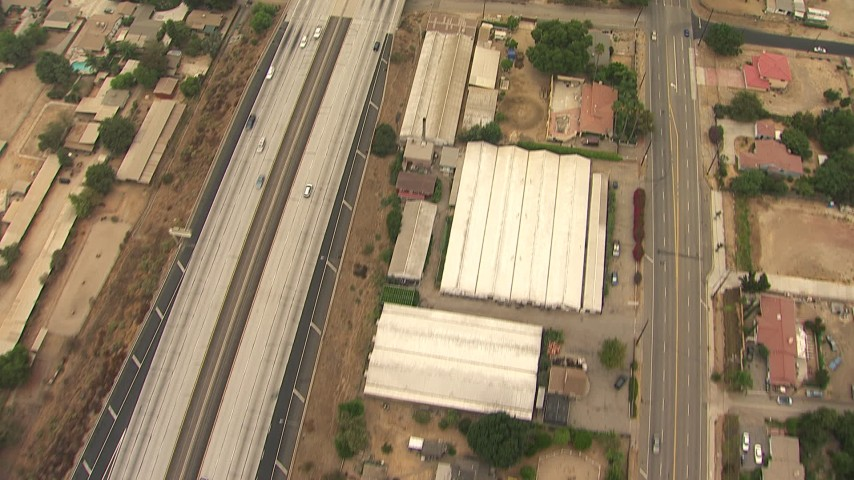 HD stock footage aerial video of bird's eye view of greenhouses and homes by the 210 Freeway, Lake View Terrace, California Aerial Stock Footage | AF0001_000415