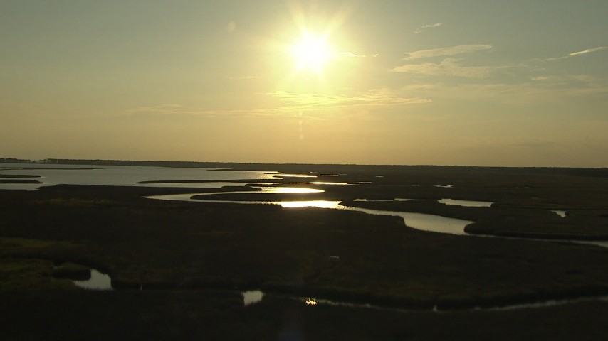 HD stock footage aerial video flyby a river through wetlands with the setting sun overhead, Gulf Coast, Alabama Aerial Stock Footage | AF0001_000419