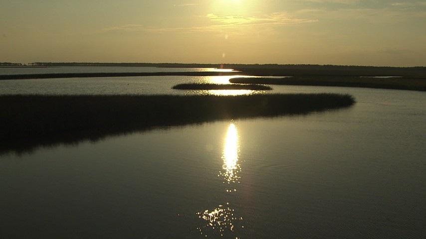 HD stock footage aerial video tilt from wetlands to reveal and fly over a river on the Gulf Coast, Alabama, sunset Aerial Stock Footage | AF0001_000420
