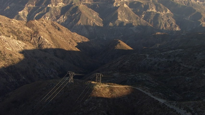 Tilt and pan across power lines through the mountains, San Gabriel Mountains, California Aerial Stock Footage | AF0001_000476