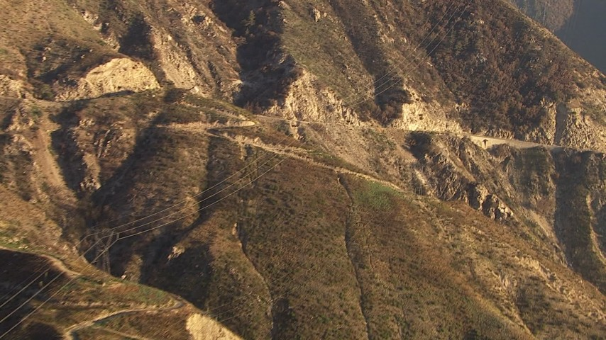 Track power lines crossing a road and up a slope in the San Gabriel Mountains, California Aerial Stock Footage | AF0001_000478