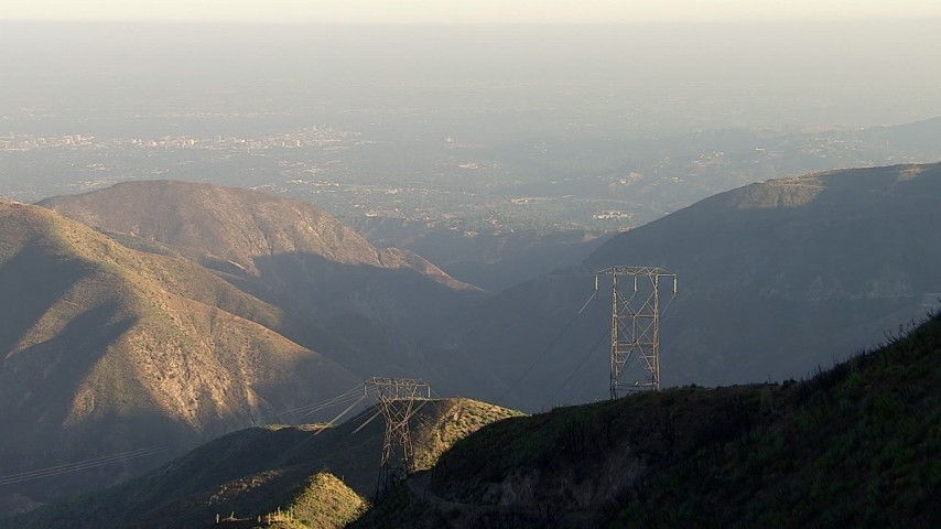 Approach a power line tower and tilt to a bird's eye view, San Gabriel Mountains, California, sunset Aerial Stock Footage | AF0001_000483