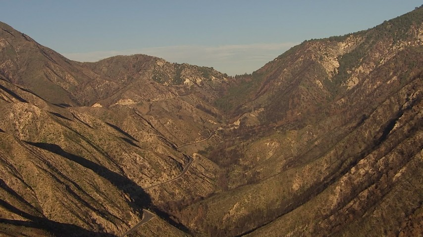 HD stock footage aerial video flyby a mountain canyon, and follow the road, San Gabriel Mountains, California, sunset Aerial Stock Footage | AF0001_000486