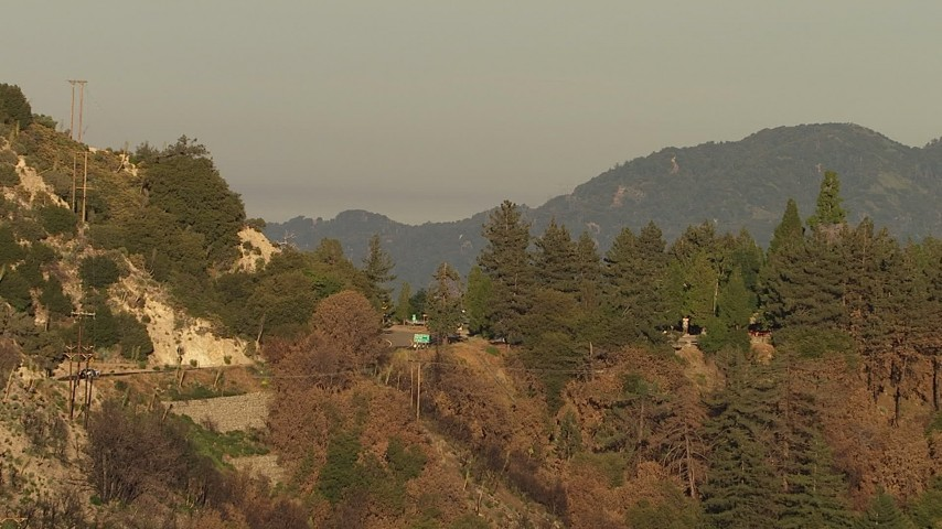 Approach and tilt to a bend in a road through the San Gabriel Mountains, California, sunset Aerial Stock Footage | AF0001_000487