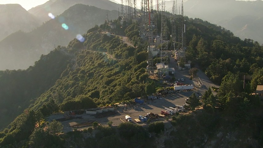 HD stock footage aerial video flyby service vehicles and parts for the radio towers on Mount Wilson, San Gabriel Mountains, California, sunset Aerial Stock Footage | AF0001_000492