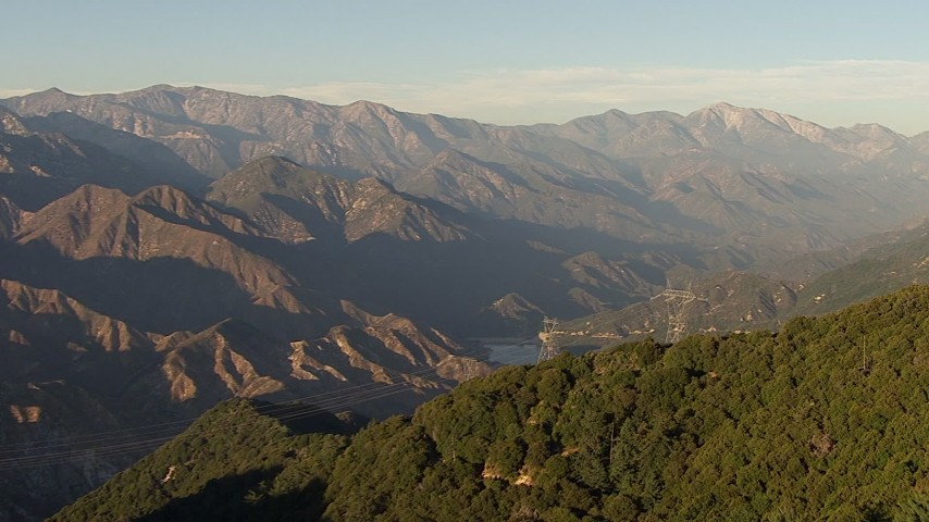 Approach power lines on a mountain ridge and tilt to a tower at sunset, San Gabriel Mountains, California Aerial Stock Footage | AF0001_000498
