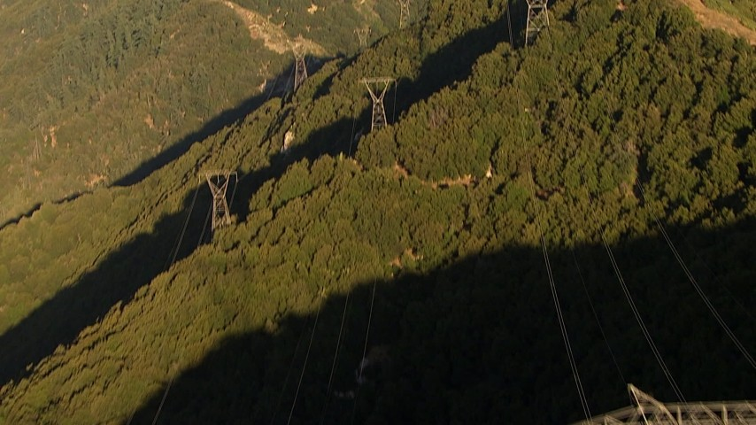 Tilt from a bird's eye view of power lines and follow them up a mountain at sunset, San Gabriel Mountains, California Aerial Stock Footage | AF0001_000499