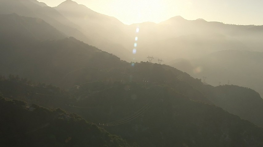 HD stock footage aerial video of passing rows of power lines through the San Gabriel Mountains, California, sunset Aerial Stock Footage | AF0001_000502