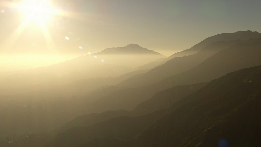 HD stock footage aerial video of the sun above power lines crossing the San Gabriel Mountains, California, sunset Aerial Stock Footage | AF0001_000506