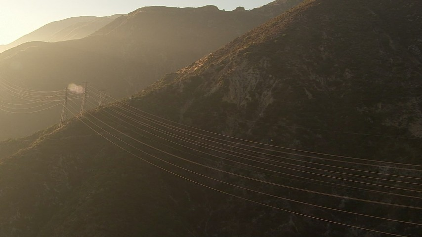 HD stock footage aerial video flyby power lines through hazy San Gabriel Mountains, California, sunset Aerial Stock Footage | AF0001_000507