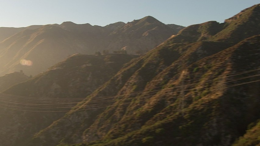 HD stock footage aerial video of passing power lines crossing hazy San Gabriel Mountains, California, sunset Aerial Stock Footage | AF0001_000508