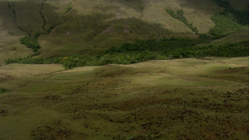 HD stock footage aerial video fly over hilly savanna to approach jungle at the base of a mountain in Southern Venezuela Aerial Stock Footage | AF0001_000538