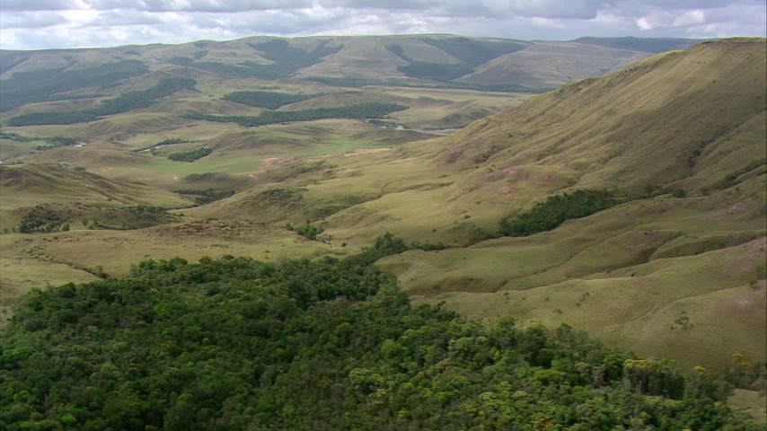 HD stock footage aerial video flying by wooded hillside, tilt  revealing savanna, Southern Venezuela Aerial Stock Footage | AF0001_000540
