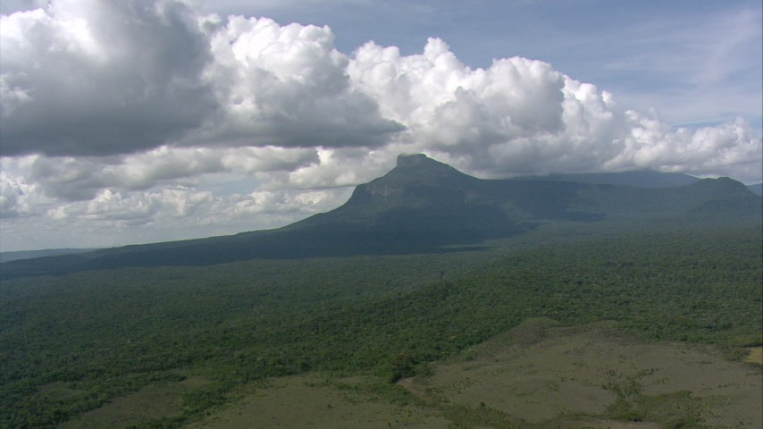Fly over jungle toward peaks and tilt to clouds overhead in Southern Venezuela Aerial Stock Footage | AF0001_000566