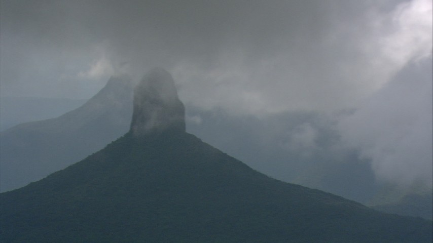 Misty clouds around a mountain peak over jungle in Southern Venezuela Aerial Stock Footage | AF0001_000595
