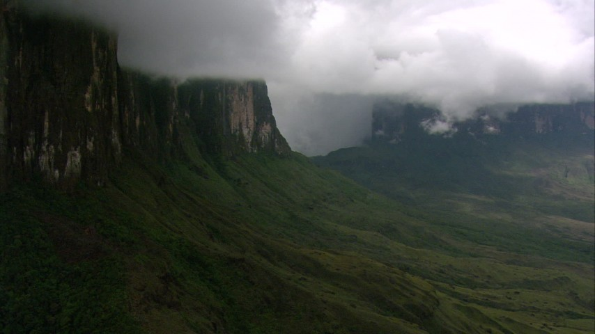 Fly through mist and over a slope to pan and reveal peaks and jungle in Southern Venezuela Aerial Stock Footage | AF0001_000609