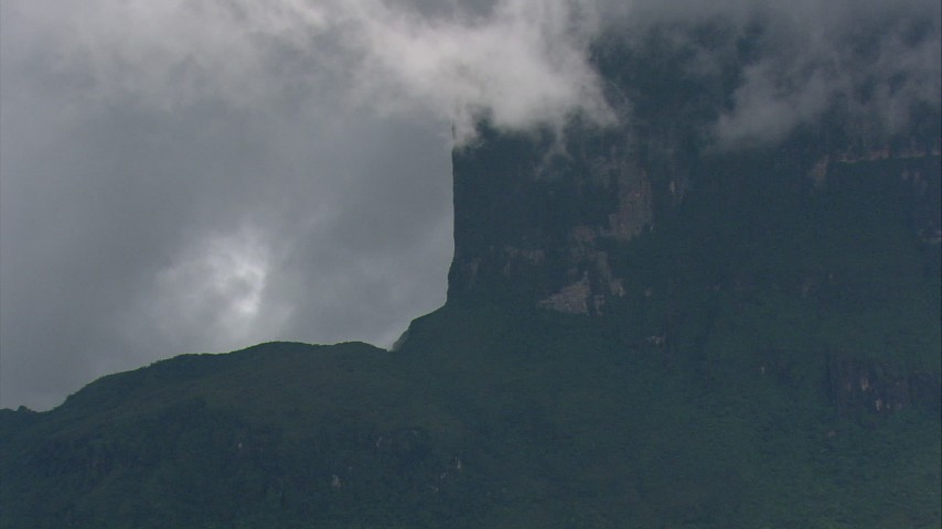 Zoom to a wider view of steep mountain cliffs and jungle with low clouds Southern Venezuela Aerial Stock Footage | AF0001_000615