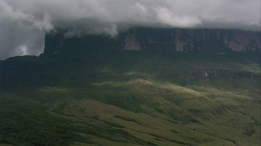 Zoom in on steep mountain slopes and jungle beneath clouds in Southern Venezuela Aerial Stock Footage | AF0001_000616
