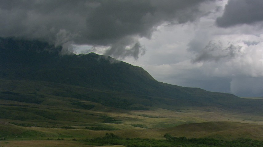 Zoom to a wider view of a rugged mountain peak and clouds in Southern Venezuela Aerial Stock Footage | AF0001_000619