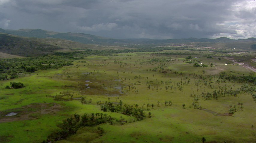 HD stock footage aerial video of reverse view of small rural town, pan across savanna to reveal mountains in Southern Venezuela Aerial Stock Footage | AF0001_000641
