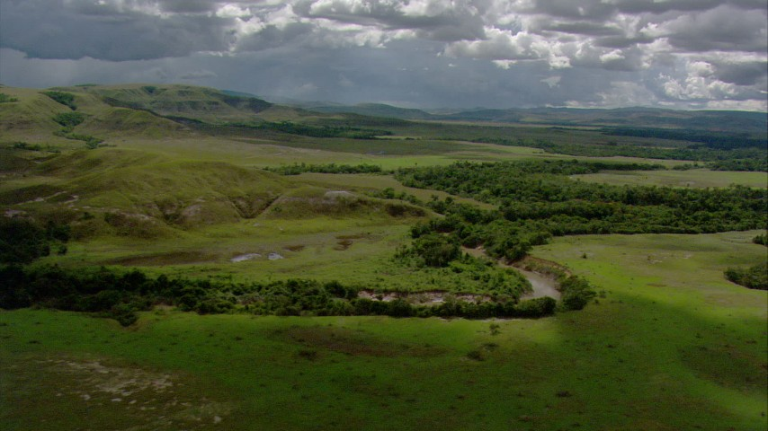 Reverse view of a river and trees beside green hills in Southern Venezuela Aerial Stock Footage | AF0001_000654