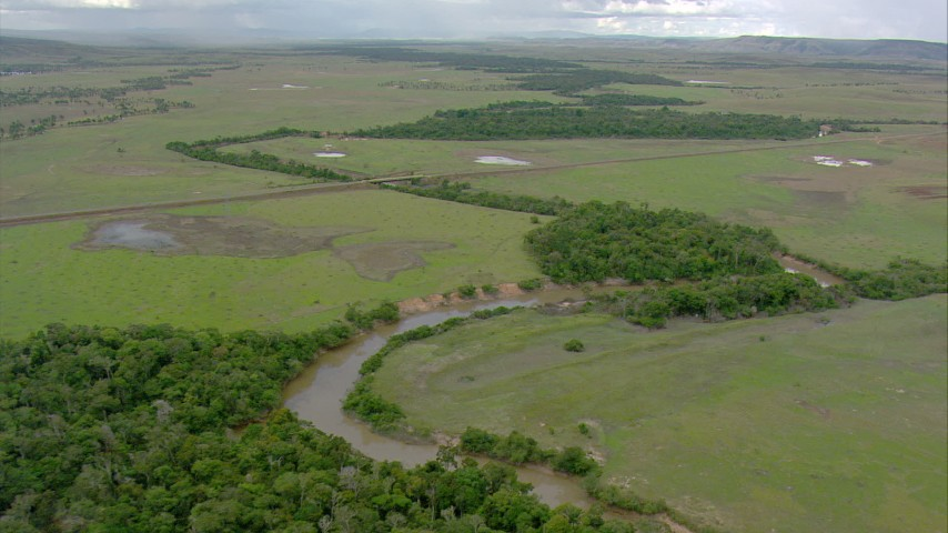 Follow the river past a patch of jungle to approach a country highway in Southern Venezuela Aerial Stock Footage | AF0001_000663