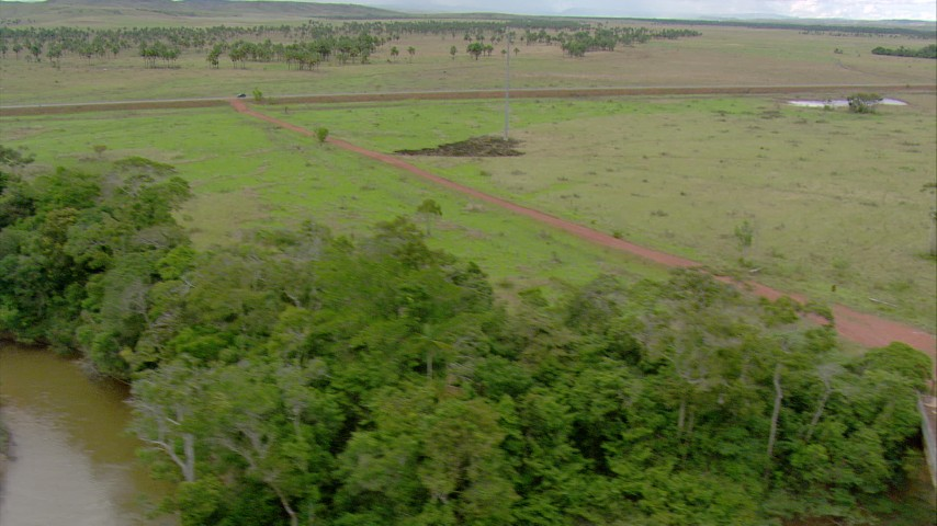 Follow the river through jungle to a bridge, tilt to the nearby highway in Southern Venezuela Aerial Stock Footage | AF0001_000666