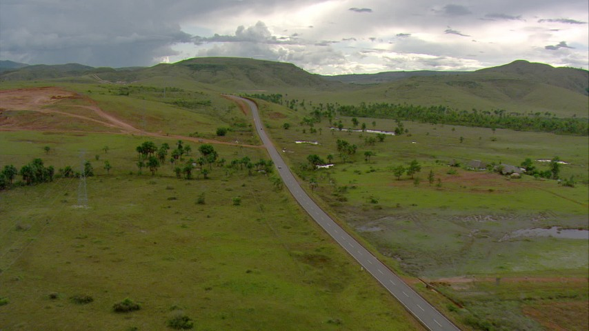 Following a country highway and approach green hills in Southern Venezuela Aerial Stock Footage | AF0001_000670