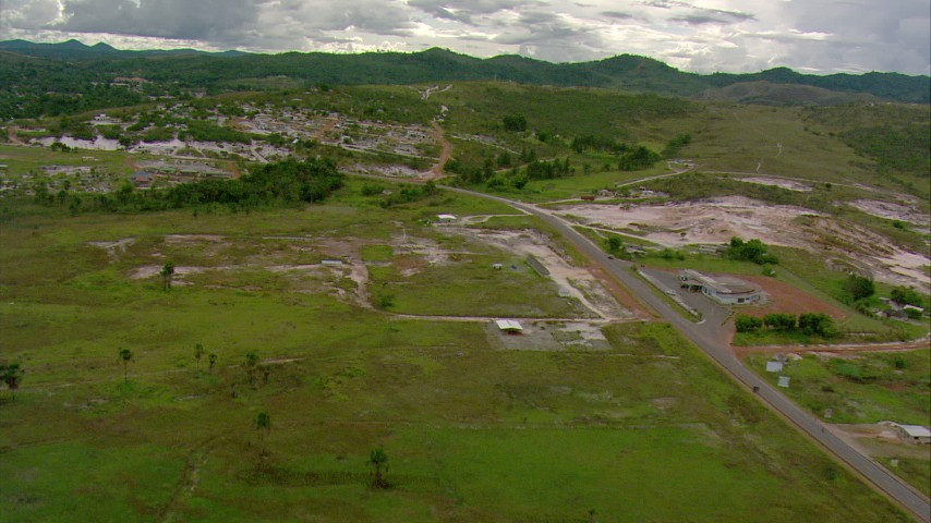 HD stock footage aerial video approach a small town by a country highway in Southern Venezuela Aerial Stock Footage | AF0001_000676