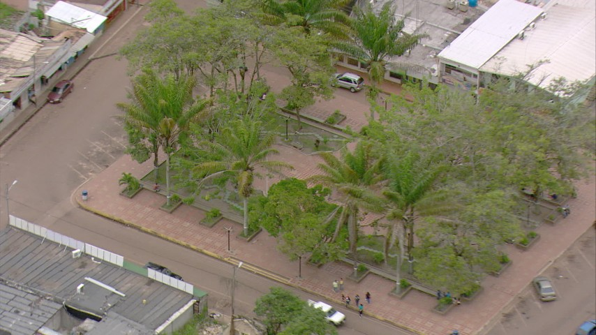HD stock footage aerial video pan across small town to reveal town park, zoom in on statue, Southern Venezuela Aerial Stock Footage   AF0001_000683