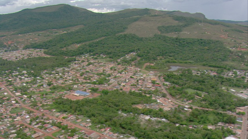 Tilt from a statue at a park to reveal the rest of the town and green mountains in Southern Venezuela Aerial Stock Footage | AF0001_000686
