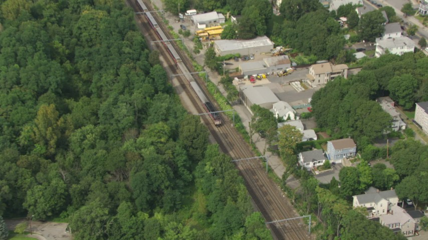 HD stock footage aerial video of a commuter train running through Hyde Park, Massachusetts Aerial Stock Footage | AF0001_000703
