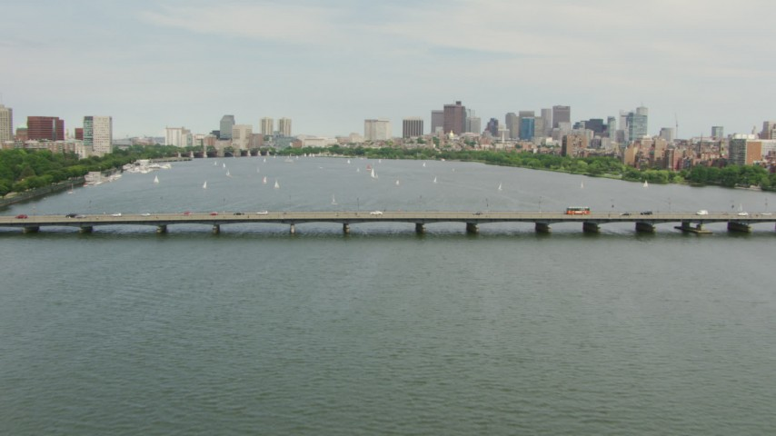 Fly over the Harvard Bridge to approach boats on Charles River and Downtown Boston, Massachusetts Aerial Stock Footage | AF0001_000739