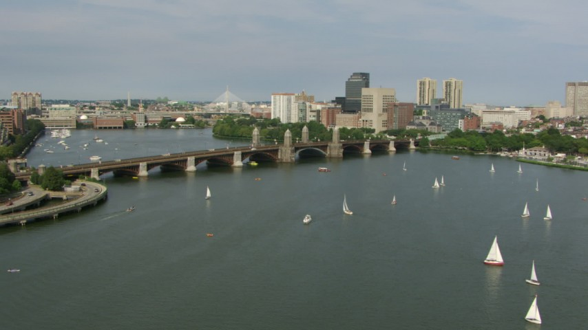 Fly over sailboats to approach the Longfellow Bridge as a commuter train crossing, Boston, Massachusetts Aerial Stock Footage AF0001_000784