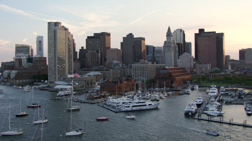 HD stock footage aerial video flyby boats at a downtown marina and riverfront skyscrapers in Downtown Boston, Massachusetts, sunset Aerial Stock Footage | AF0001_000792