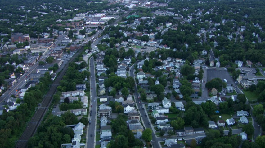 HD stock footage aerial video of flying over a residential neighborhood by train tracks in Hyde Park, Massachusetts, twilight Aerial Stock Footage | AF0001_000813