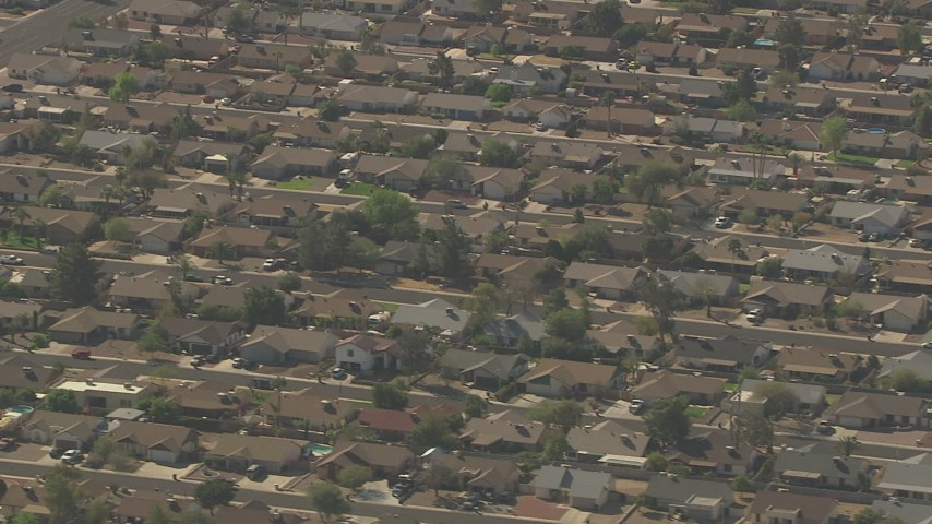 Flying by homes in a suburban residential neighborhood, Peoria, Arizona Aerial Stock Footage AF0001_000830 | Axiom Images