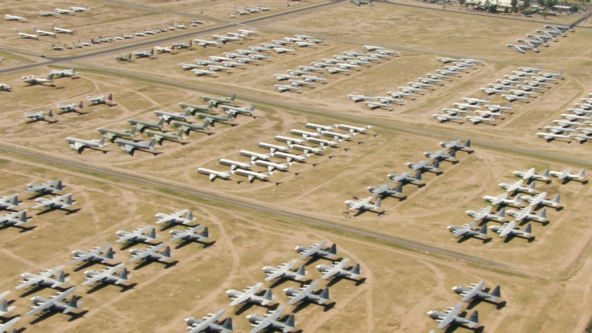Military jet and prop airplanes at an aircraft boneyard, Davis Monthan AFB, Tucson, Arizona Aerial Stock Footage | AF0001_000861