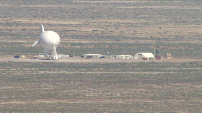 Flying by a blimp at a small airfield, Arizona Desert Aerial Stock Footage | AF0001_000880
