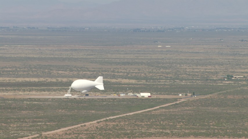 HD stock footage aerial video of a white blimp at an airfield in the middle of the Arizona Desert Aerial Stock Footage | AF0001_000886