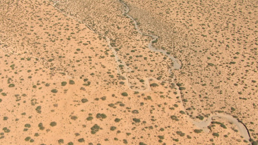 Bird's eye view of a dry creek bed through desert, New Mexico Aerial Stock Footage AF0001_000889