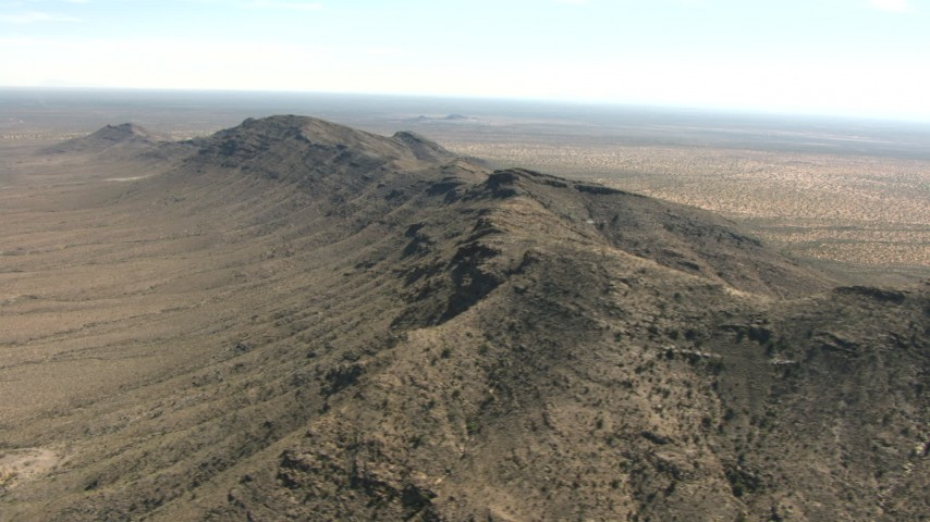 Flying by a desert mountain ridge, New Mexico Aerial Stock Footage | AF0001_000892