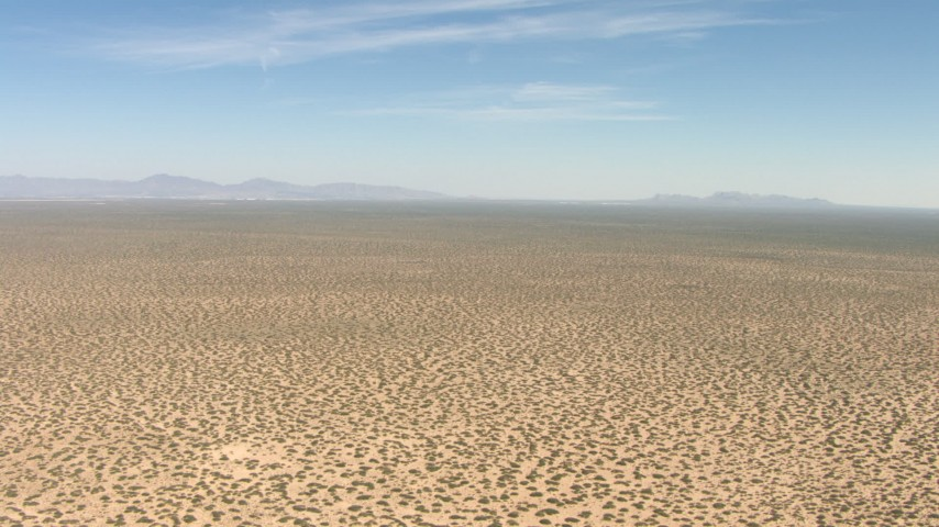 Flying over a dry desert plain in New Mexico Aerial Stock Footage | AF0001_000895