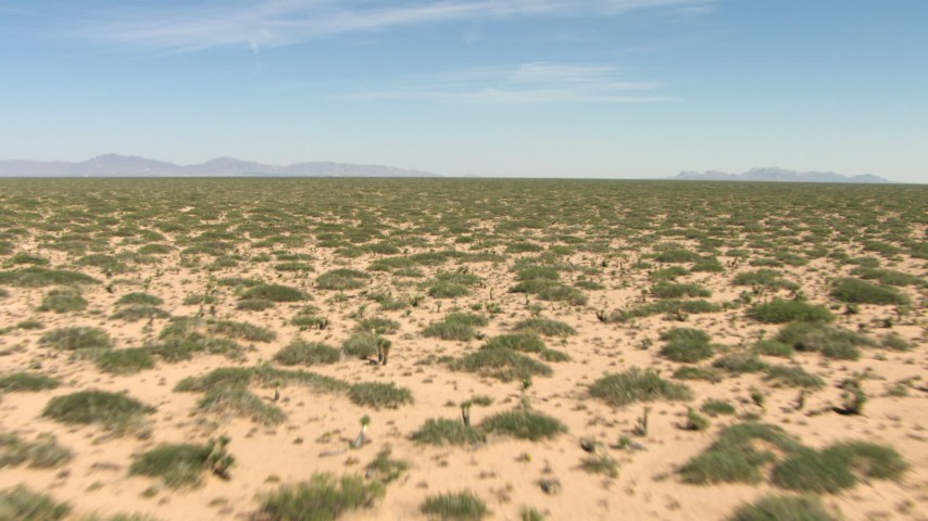 A wide plain with desert vegetation in New Mexico Aerial Stock Footage | AF0001_000902